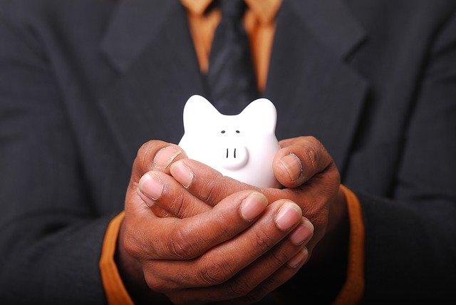 Mann hält kleines sparschwein in der Hand